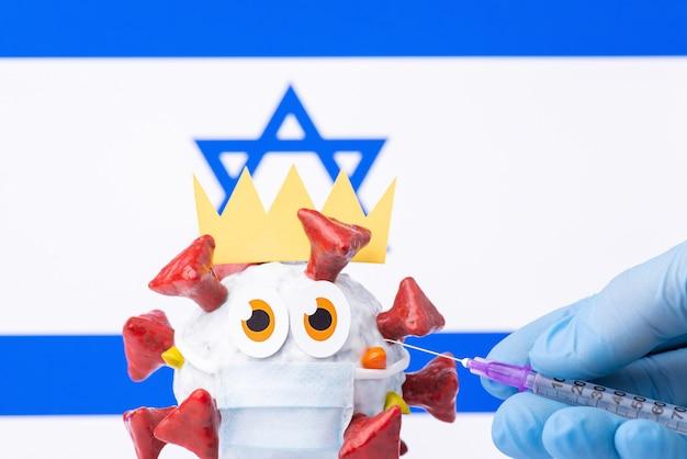 Animiertes coronavirus-modell mit krone und medizinischer maske mit einer flagge von israel im hintergrund