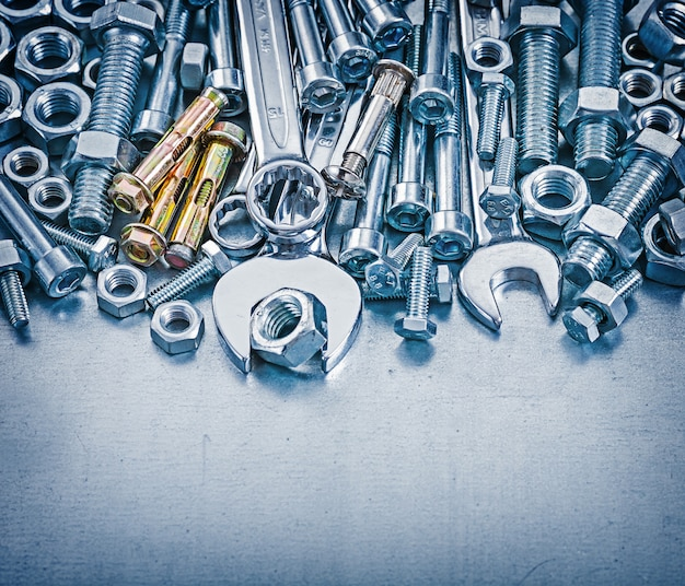 Ankerbolzen bolzendetails muttern hakenschlüssel und flacher schraubenschlüssel auf metallischem hintergrundkonstruktionskonzept