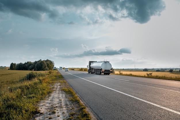 Ankunft des weißen lastwagens auf der straße in einer ländlichen landschaft bei sonnenuntergang