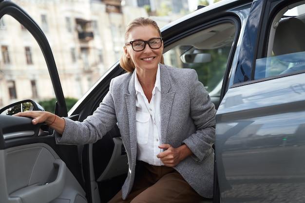 Ankunft im büroporträt einer attraktiven und glücklichen geschäftsfrau, die eine brille trägt