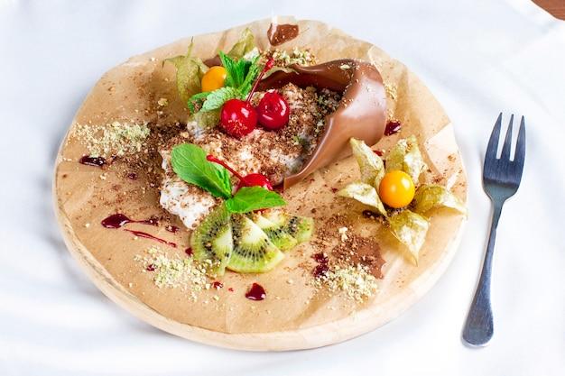 Anlage des schokoladennachtischs mutter mit sahne und frischen früchten auf rundem brett