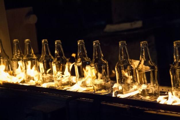 Anlage zur herstellung von glasflaschen. glasflaschen auf einem förderband mit feuer