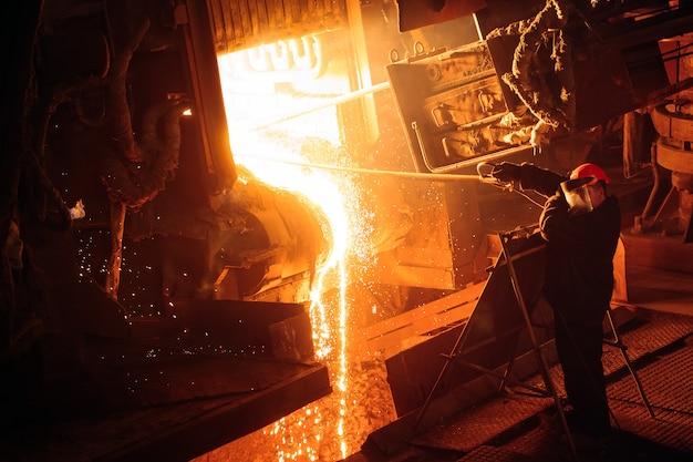 Anlage zur herstellung von stahl. ein elektrischer schmelzofen. fabrikarbeiter nimmt eine probe für metall.