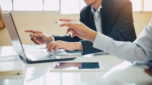 Anlageberater mit zwei geschäftsmännern, der firmenfinanzbericht analysiert