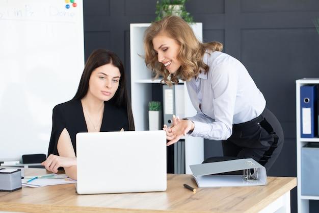 Anlageberaterin für zwei geschäftsfrauen, die den jahresfinanzbericht des unternehmens analysiert