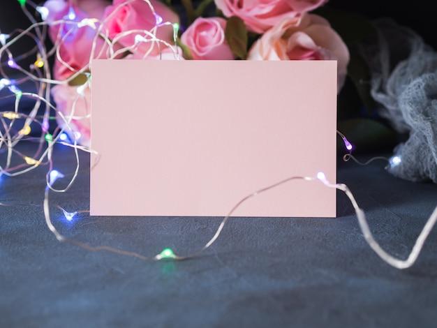 Anmerkung des leeren papiers der valentinstaggrußkarteneinladung mit bunten lichtern auf dunklem hintergrund mit rosen