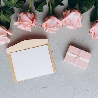 Anmerkung des leeren papiers mit umschlag, geschenken und rosarose