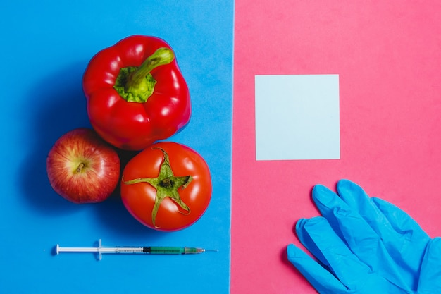 Anmerkung, grüne flüssigkeit in der spritze, rote tomate, apfel, pfeffer, blaue handschuhe.