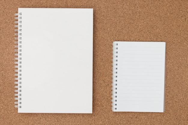 Anmerkungsbuchpapier auf korkenbrett.
