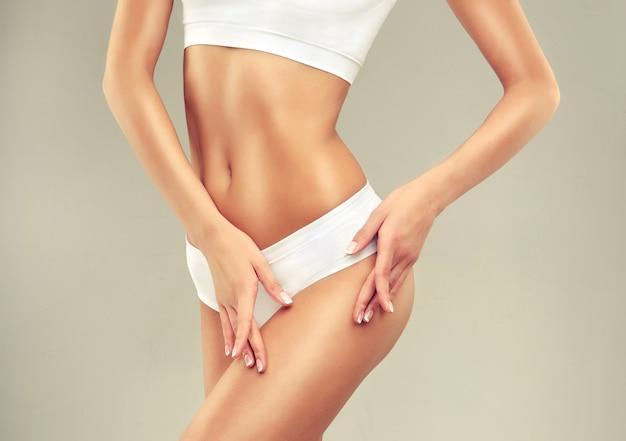 Anmutig aussehender frauenkörper in weißer sportunterwäsche schlanker körper und elegante handgeste