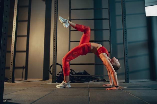 Anmutig. junge muskulöse kaukasische frau, die im fitnessstudio übt. sportliches weibliches model, das kraftübungen macht, ihren unter- und oberkörper trainiert und sich streckt. wellness, gesunder lebensstil, bodybuilding.