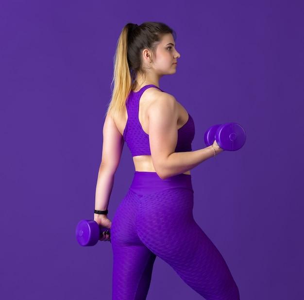 Anmutig. schöne junge sportlerin üben, einfarbiges lila porträt. kaukasisches modell der sportlichen passform mit gewichten. bodybuilding, gesunder lebensstil, schönheits- und aktionskonzept.