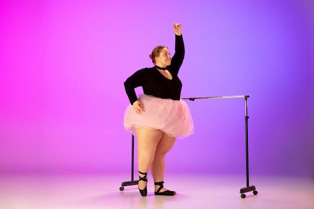 Anmutig. schönes kaukasisches plus-size-model, das balletttanz auf einem lila-rosafarbenen studio mit farbverlauf übt