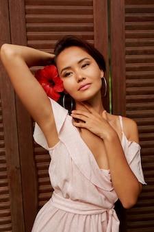 Anmutige asiatische frau mit perfekter haut und hibiskusblume in den haaren, die über holzwand aufwerfen