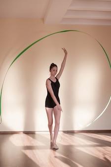 Anmutige ballerina in bewegung. rhythmische gymnastik. jugendsport, gesunder jugendlicher lebensstil. selbstbewusstes mädchen mit grünem band, tanzkurshintergrund mit freiem raum, übungskonzept