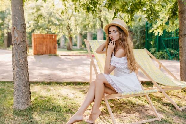Anmutige barfüßige dame im strohhut, die auf chaiselongue mit nachdenklichem gesichtsausdruck sitzt. außenporträt des hübschen langhaarigen mädchens im weißen kleid, das auf stuhl im park kühlt.