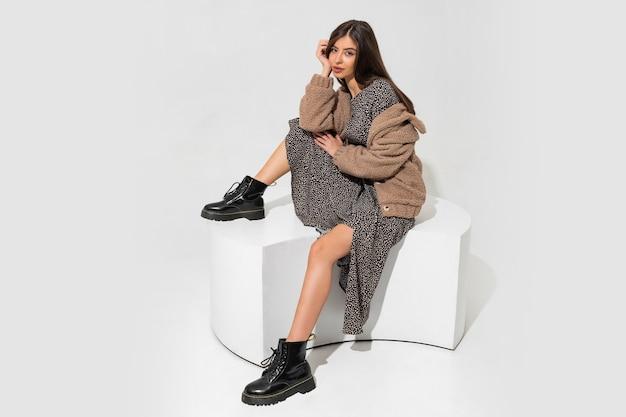 Anmutige europäische frau im winterpelzmantel und im stilvollen kleid sitzen. stiefelette aus schwarzem leder.