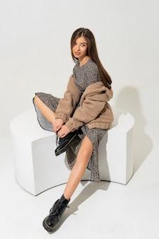 Anmutige europäische frau im winterpelzmantel und im stilvollen kleid sitzen.