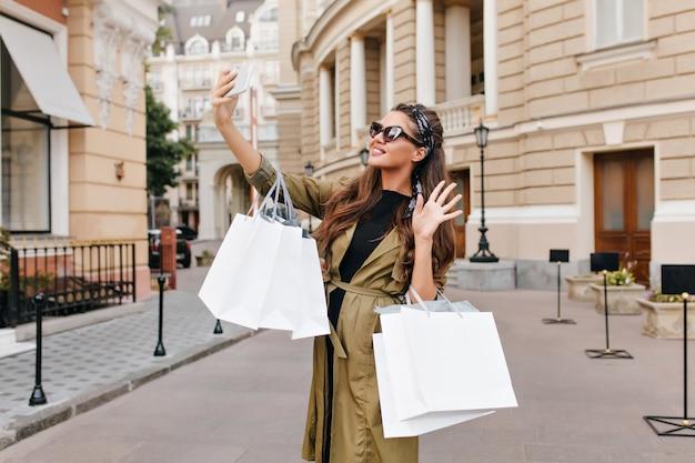 Anmutige fashionista frau trägt grünen mantel, der selfie auf der straße macht