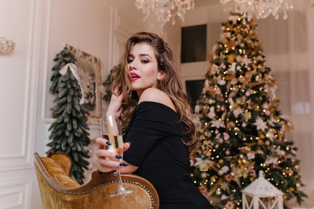 Anmutige, faszinierende dame in der schwarzen spitze, die für träger gegen geschmückten weihnachtsbaum aufwirft und glas weißwein hält