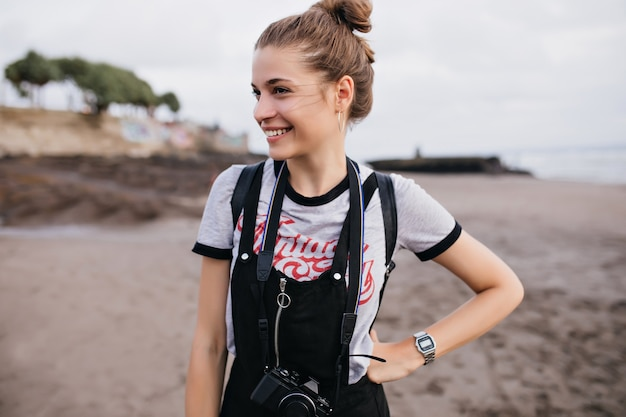 Anmutige fotografin, die in der selbstbewussten haltung am strand steht. angenehmes mädchen in der trendigen armbanduhr, die auf natur lächelt.