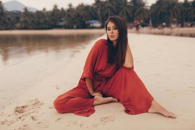 Anmutige frau, die am strand aufwirft, sitzt auf sand im roten kleid