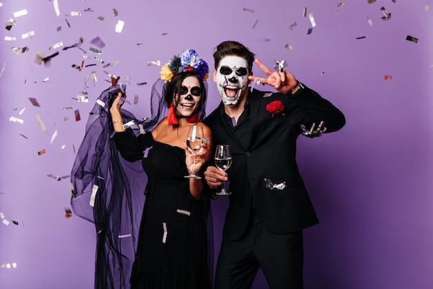 Anmutige frau im bunten kranz, der halloween mit freund feiert. paar vampire, die champagner trinken.