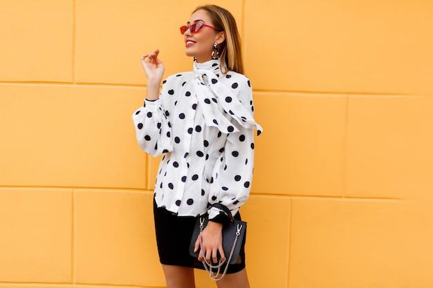 Anmutige frau im stilvollen lässigen outfit, das mit luxusledertasche des schwarzen leders aufwirft.
