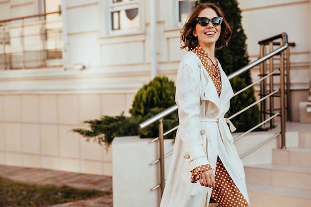Anmutige frau im weißen kittel und in der sonnenbrille, die glückliche gefühle ausdrückt. außenaufnahme der schönen dame im eleganten herbstoutfit.