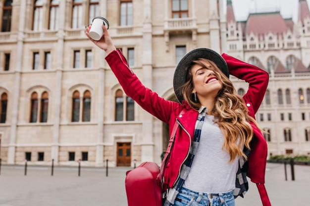 Anmutige frau in der trendigen freizeitkleidung, die am wochenende europäische reisen genießt