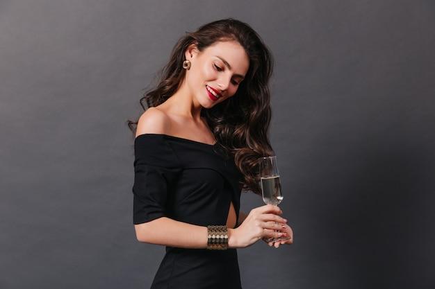 Anmutige frau mit gewelltem langem haar und im stilvollen schwarzen kleid, das mit champagner auf dunklem hintergrund aufwirft.