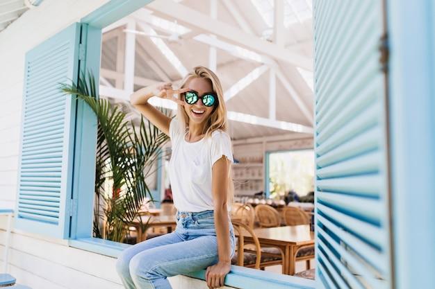 Anmutige glückliche frau, die auf fensterbank sitzt und mit ihren blonden haaren spielt.