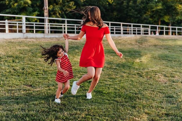 Anmutige junge dame im kurzen roten kleid, das hände mit tochter hält. foto in voller länge von mutter und kind, die im park spielen.