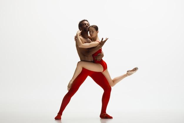 Anmutige klassische balletttänzer tanzen isoliert auf weißer wand. das konzept von anmut, künstler, bewegung, aktion und bewegung.