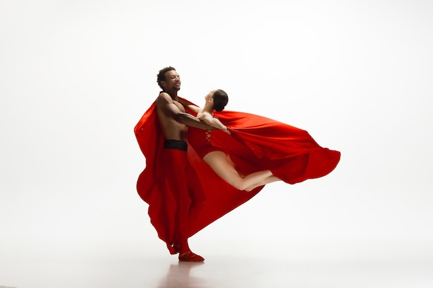 Anmutige klassische balletttänzer tanzen lokalisiert auf weißem studiohintergrund. paar in knallroten kleidern wie eine kombination aus wein und milch. das konzept von anmut, künstler, bewegung, aktion und bewegung.