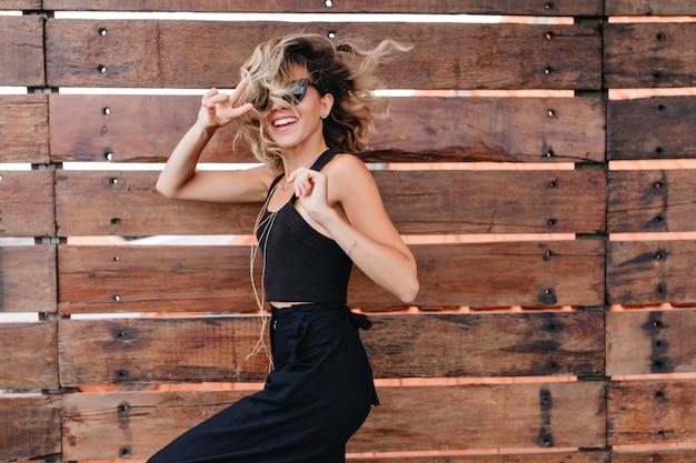 Anmutige kurzhaarige frau in stilvoller sonnenbrille, die spaß während des fotoshootings hat. schönes gebräuntes mädchen in der eleganten schwarzen kleidung, die auf holzwand aufwirft.
