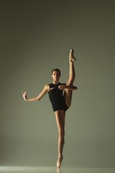 Anmutiger balletttänzer oder klassischer ballerina-tanz lokalisiert auf grauem studiohintergrund. flexibilität und anmut zeigen. das tanz-, künstler-, zeitgenossen-, bewegungs-, aktions- und bewegungskonzept.