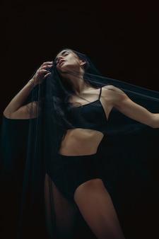 Anmutiger klassischer balletttänzer, der lokalisiert auf schwarzem studiohintergrund tanzt.