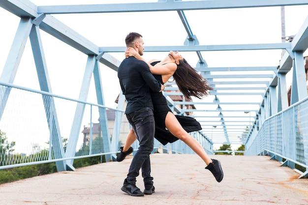 Anmutiger tänzer, der auf der brücke tangoing ist