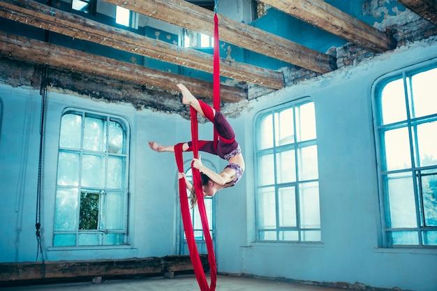 Anmutiger turner, der luftübung mit roten stoffen auf blauem altem dachboden durchführt