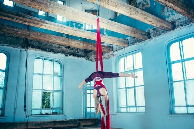 Anmutiger turner, der luftübung mit roten stoffen auf blauem altem dachbodenhintergrund durchführt. junges jugendliches kaukasisches fit mädchen. der zirkus, akrobatik, akrobat, performer, sport, fitness, gymnastikkonzept