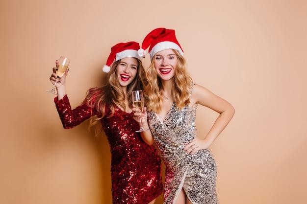 Anmutiger weiblicher weihnachtsmann, der becher mit champagner erhebt, der nahe charmanten lockigen freund aufwirft