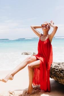 Anmutiges barfußes mädchen, das auf stein mit niedlichem lächeln aufwirft. foto im freien der positiven jungen frau in den roten kleidern, die spaß am strand haben.