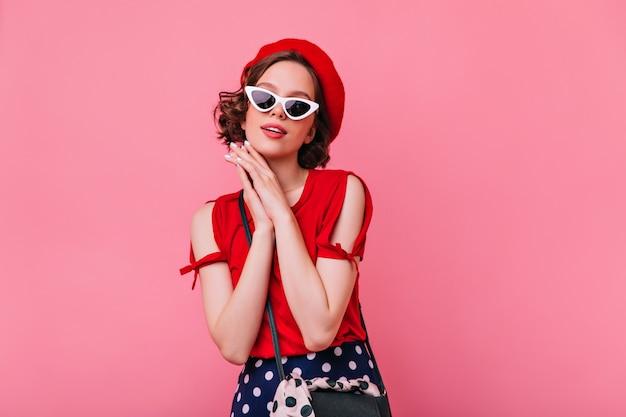 Anmutiges blasses mädchen im stehenlassen der französischen baskenmütze. optimistische brünette frau in der sonnenbrille, die aufwirft.
