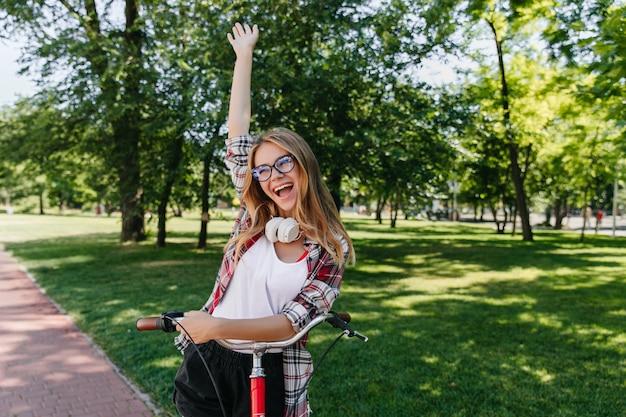 Anmutiges blondes mädchen, das aufregung ausdrückt. außenfoto der fröhlichen weißen dame mit dem fahrrad, das auf park aufwirft.