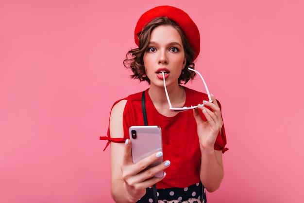 Anmutiges ekstatisches mädchen mit sonnenbrille, die spielerisch aufwirft. charmante französische frau mit smartphone in der hand stehend.