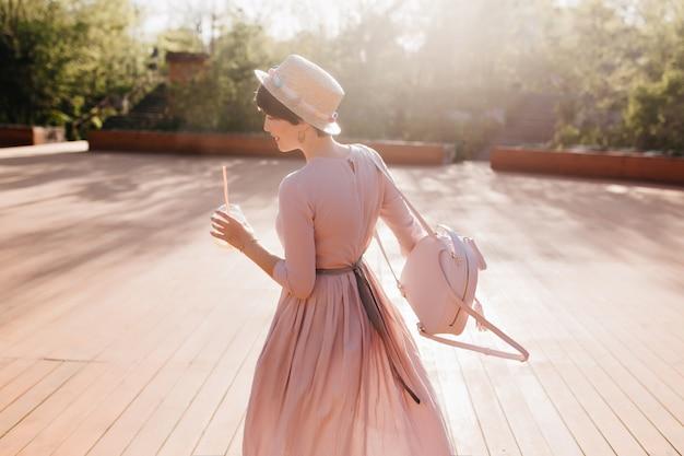Anmutiges formschönes mädchen im retro-kleid, das draußen unter sonnenlicht tanzt und trendigen rucksack hält
