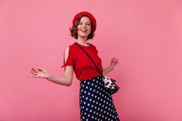 Anmutiges französisches weibliches modell, das genießt. porträt des sinnlichen kaukasischen mädchens in der roten baskenmütze und im schwarzen rock.