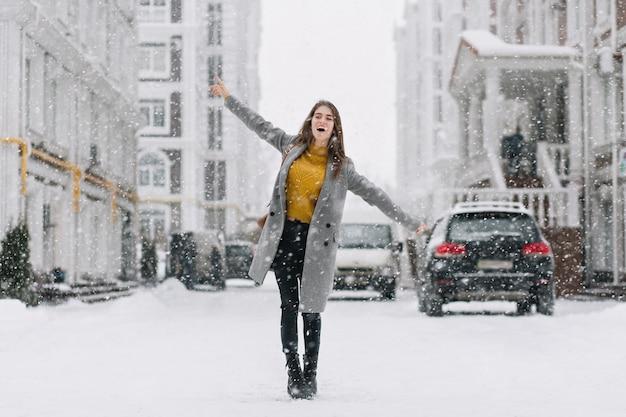 Anmutiges kaukasisches weibliches modell im langen mantel, der auf der straße im wintermorgen tanzt. außenfoto der bezaubernden dame im gelben pullover, der hände während des fotoshootings am frostigen tag winkt.