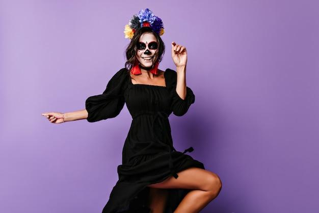 Anmutiges lachendes mädchen im schwarzen kleid, das am tag der toten tanzt. freudige lateinamerikanische dame mit zombie-make-up, die halloween feiert.
